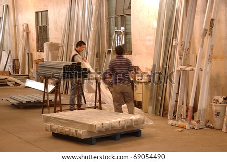 CANTON, CHINA - NOVEMBER 11: One of the biggest manufacturer of auto spray booths and generators in China. Workers unpack raw material for production on November 11, 2010 in Canton, China.