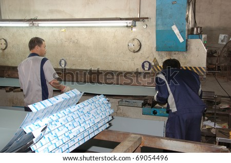CANTON, CHINA - NOVEMBER 11: One of the biggest manufacturer of auto spray booths and generators in China. Workers with aluminum folding profiles machine on November 11, 2010 in Canton, China.