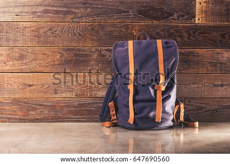 Canvas and leather backpack on wooden wall