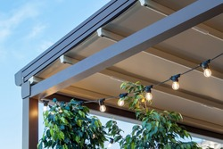 canvas awning with metal frame and luminous garland of light bulbs against blue sunny sky. modern shading for house
