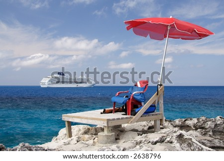 Canvas chair and parasol with a cruiseship in the background