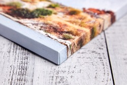Canvas print on wooden background. Wrapped canvas, edge, corner, closeup. Detail of stretched landscape photography with gallery wrapping. Photo printed on canvas