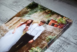 Canvas print. Photo printed on canvas. Sample of stretched wedding photography with gallery wrap, side view, closeup. Portrait on grey wooden surface