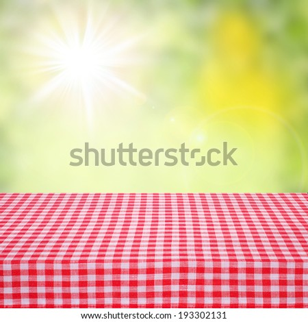 Canvas texture or background on table. Red checked tablecloth view from top. Empty tablecloth for product montage. Sunny summer day outdoors. Free space for your text