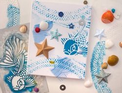 canvas with stencil printed fish drawing. Clam shells glazed with acrylic paint. Summer theme craft.