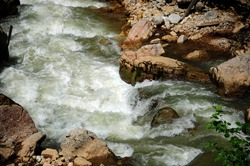 canyon of a stormy river in a mountain forest waterfall, horizontal background texture image, blurred, soft focus, copy space