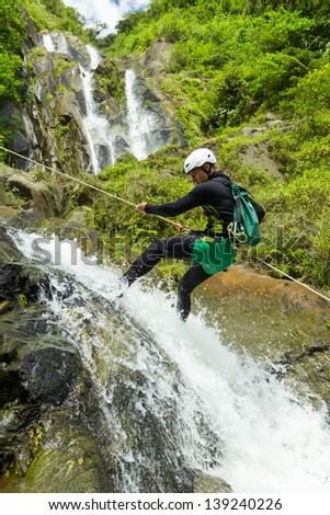 Canyoning guide trying out a new route in Chama waterfall, Banos De Agua Santa, Ecuador