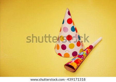 Cap and pipe for a party. On a yellow background