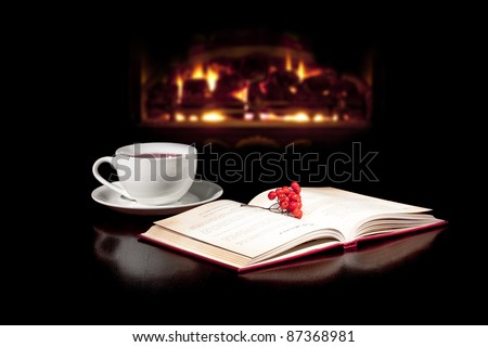 Cap of tea and book on the table top with fireplace in the background. - stock photo