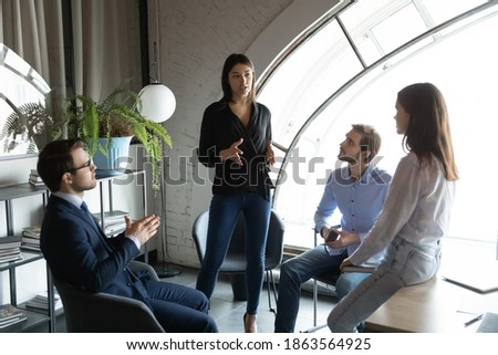 Capable qualified indian female business trainer coach explain learning material to diverse group of young students interns colleagues on intensive course workshop seminar in office or coworking space Photo stock ©
