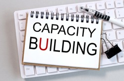 capacity building, text on white paper on white keyboard background