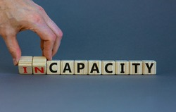 Capacity or incapacity symbol. Businessman turns wooden cubes and changes the word 'incapacity' to 'capacity'. Beautiful grey background. Business and capacity or incapacity concept. Copy space.