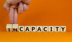 Capacity or incapacity symbol. Businessman turns wooden cubes and changes the word 'incapacity' to 'capacity'. Beautiful orange background. Business and capacity or incapacity concept. Copy space.