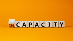 Capacity or incapacity symbol. Turned a wooden cube and changed the word 'incapacity' to 'capacity'. Beautiful orange background. Business and capacity or incapacity concept. Copy space.