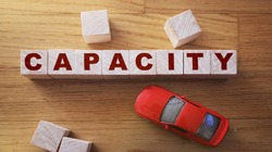 Capacity word made of wooden cubes on a wooden background with red toy car. Business capacity logistic management concept.