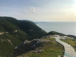 Cape Breton Highlands National Park. The view of Skyline Trail with a boardwalk with steps, Cabot Trail Road, and the Atlantic Ocean. Sunset time. Cape Breton Island, Nova Scotia, Canada