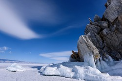 Cape Burhan on Shamanka Rock in Olkhon island covered with icicles in sunny march day. Lake Baikal with amazing clouds