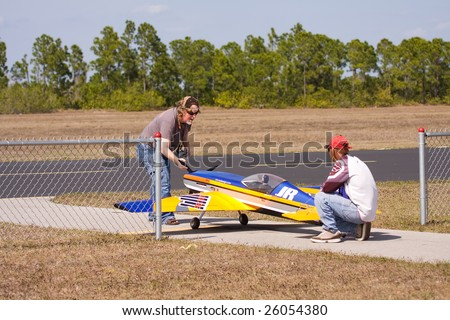 CAPE CORAL, FL. - FEBRUARY 22:  Alex Miller (R) holds David deMoya's (L) aircraft in Cape Coral, Florida as he starts the engine for the coming Gathering of the Giants air show on March 21 & 22, 2009.