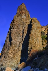 Cape Fiolent, high sharp ancient basalt rock, cliff stands on Black Sea stones coast, in the light of sunset with shadows against the backdrop of blue summer sky, Crimea