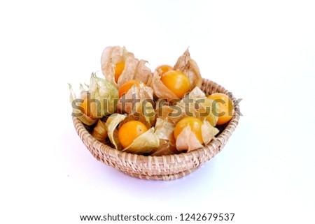 cape gooseberry in wicker basket on white background
