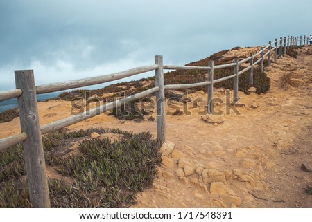 Cape of Rock (Cabo da Roka) in Portugal. Surroundings, wooden fence, deserted yellow clay and greenery. Stok fotoğraf ©