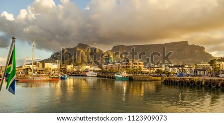 Cape Town harbor, Victoria and Alfred Waterfront at sunset with south african flag. Table mountain in background, South Africa beautiful destination #1123909073