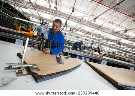 CAPE TOWN, SOUTH AFRICA - AUG 2: A man cuts fabric for a new garment in a large clothing factory in Cape Town, South Africa on August 2, 2012