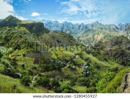 Cape Verde. Gorgeous panoramic view of famous fertile Paul Valley. Agriculture terraces of sugarcane in vertical valley sides, people dwellings, rugged peaks and motion clouds on horizon #1280455927