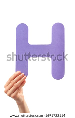 Capital letter H held in woman's hand on white background Stock fotó ©