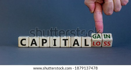Capital loss or gain symbol. Male hand turns cubes and changes words 'capital loss' to 'capital gain'. Beautiful grey background. Business and capital loss or gain concept. Copy space.