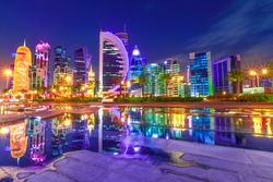 Capital of Qatar. Colorful Doha West Bay high rises illuminated at night reflections in downtown park. Scenic towers of Doha skyline, Middle East, Arabian Peninsula in Persian Gulf. Violet colors shot