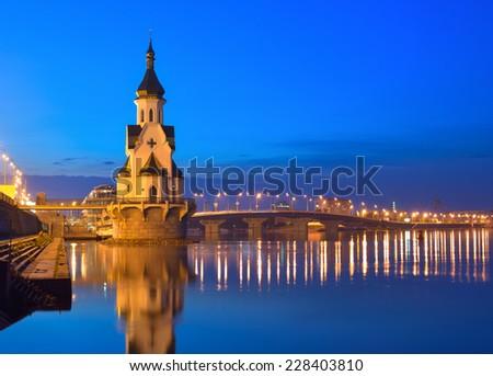 Capital of Ukraine, Kyiv. Church of Saint Nicholas on the water, old embankment and Havanskyi Bridge in Kiev at night.