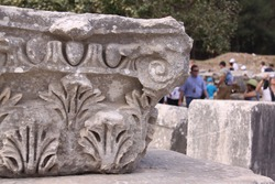 Capital part of a corinthian style column  and bokeh background of tourists visiting an archeological site