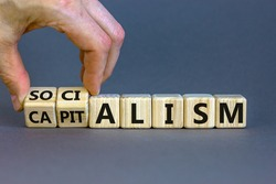 Capitalism or socialism. Hand turns cubes and changes word 'capitalism' to 'socialism'. Beautiful white background, copy space. Business and capitalism or socialism concept.