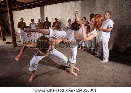 Capoeria martial artists performing techniques on concrete floor