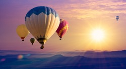 Cappadocia at sunrise - landscape with hot air balloons flying over mountain valley in sunlight and mist. Adventures on Turkey - travel concept background, romantic holiday or ballooning festival.