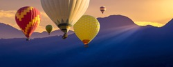 Cappadocia at sunrise - many colorful hot air balloons flight above mountains. Panoramic landscape with blue silhouettes of mountains and balloons for your concept of travel, adventures or dreams.