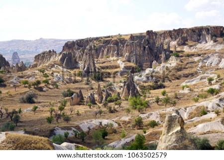 "Cappadocia, Kapadokya Otelleri, semi-arid region in central Turkey, is known for its distinctive ""fairy chimneys,"" tall, cone-shaped rock formations clustered in Monks Valley, Göreme, Turkey #1063502579"