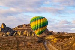 Cappadocia, Turkey / January 12, 2020: Hot air balloons landing over spectacular Cappadocia. Beautiful view of colorful hot air balloons floating in sunrise light.