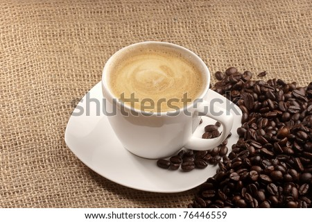 cappuccino and coffee beans over sacking