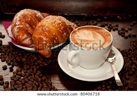 Cappuccino and croissant with coffee bean