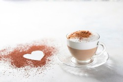 Cappuccino and heart made of cocoa powder on white background. The idea for a festive breakfast, Valentine's Day. Selective focus, copy spacy