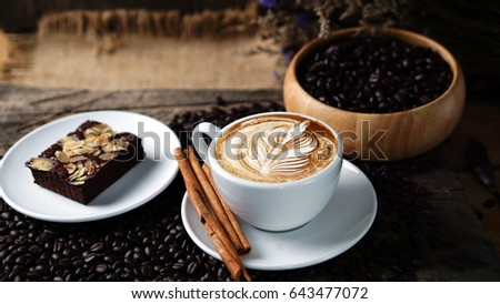 Cappuccino and sweet chocolate brownies cake. A cup of latte, cappuccino or espresso coffee with milk put on a wood table with dark roasting coffee beans. Latte art by milk on top with flowers.