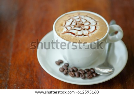 Cappuccino art coffee on wooden table  #612595160