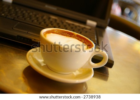 Cappuccino coffee and laptop,  shallow DOF(far froth is sharp)
