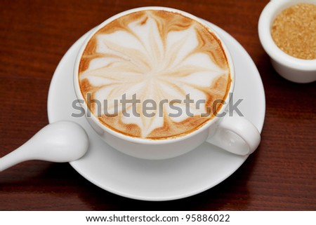 cappuccino, coffee cup and cane sugar on table