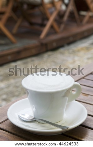 Cappuccino coffee cup outdoor in the street cafe over blur background
