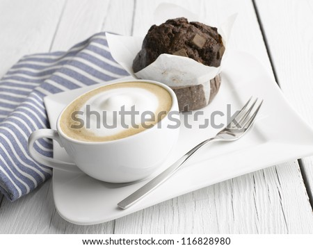 Cappuccino coffee cup with muffin on white table