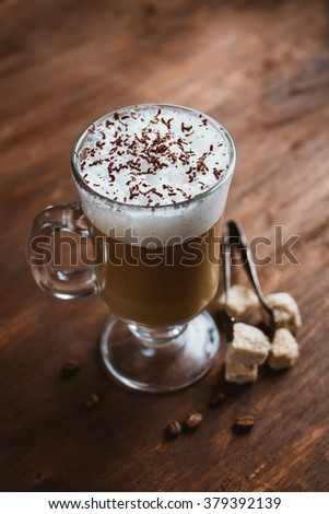 Cappuccino coffee in a glass on a brown wooden table. Selective focus. #379392139