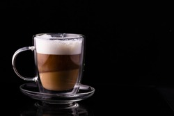 Cappuccino coffee in a transparent cup on a black background.